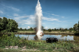 A plume of water shoots into the sky after liquid explosives are detonated underwater. The explosives were tested to see if they would be a viable solution to detonate UXO underwater. The test took place at the divers training centre in Kampong Chhanang Province, Cambodia.