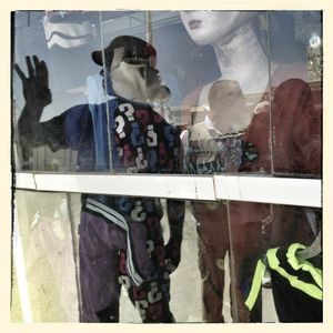 Reflection of photographer Michael Christopher Brown in a shop window in Za'atari refugee camp.