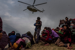 Nepalese villages watch a helicopter picking up a medical team, dropping aid atthe edge of a makeshift landing zone in Gumda, Nepal, 09 May 2015.