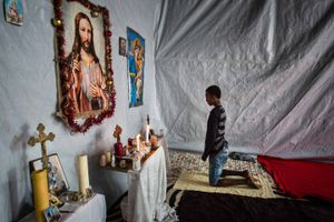 August 2015, Calais, France. A refugee prays in a big tent made up as a catholic church in the Jungle Camp, Calais. Many refugees want to go to the UK because they have family there, speak English or hope for good job opportunities.