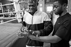Coach helps young boxer to wrap his arms the right way with the elastic band. It is one of the most important routines before training or fight and it is requires precision. Only a correctly wrapped hand is safe from bad harm.
