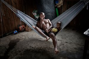An Arara warrior relaxes on his hammock with his son after lunch in the Arara indigenous village of the Big Bend of the Xingu. The whole tribe is among the most affected by the construction of the dam.  © Dario Bosio/Parallelozero