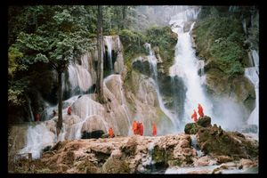Sacred Water, Laos. Monks in Tad Khuang Si admire the cascades' pure water, which is a part of many Buddhist rituals. As a token of respect and purification, monks and sacred statues are sprinkled with holy water during ordination ceremonies and Lao New Year festivities. © Lâm Duc Hiên