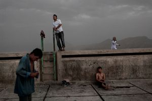 Afghan people seen at a Soviet-era swimming pool atop Swimming Pool Hill in Kabul, Afghanistan on July 20, 2008. © Adam Ferguson