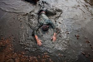 The Taiwanese army is known for its exceptionally long and hard compulsory national service. A soldier crawls in mud in the Kaoshiung mudfields. © Touko Hujanen