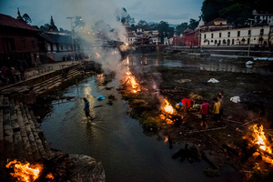 Flames rise from burning funeral pyres during the cremation of earthquake victims at the Pashupatinath Temple on the banks of Bagmati River, Kathmandu,Nepal, 28 April 2015.