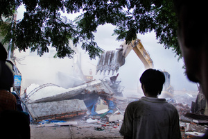 A boy watches an excavator as it approaches the new company's offices in Boeung Kak.
