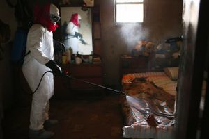 "Bedroom. A burial team sprays disinfectant over the body of a woman suspected of dying of Ebola in her home. From the series ""Ebola Crisis Overwhelms Liberian Capital."" Winner of L'Iris d'Or, 2015 Sony World Photography Awards."