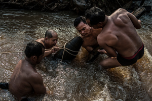The UXO salvage dive team handle an unexploded 1000 pound bomb found in a river in Kratie Province, Cambodia.