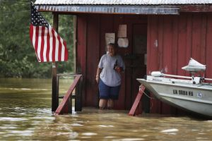 """""""A person is seen on the front porch of a home as it is surrounded by flood waters in Port Vincent, Louisiana"""". From the Series """"Louisiana Flooding""""."""