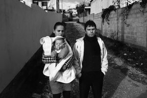 A young couple and their baby. In Albania, marriages usually occur at a very young age, especially for the girls. Tirana, Albania © Enri Canaj