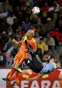 1st Prize Sport Single © Mike Hutchings, South Africa, for Reuters. Netherlands Demy de Zeeuw is kicked in the face by Uruguays Martin Cáceres during World Cup semi-final, Cape Town, 6 July