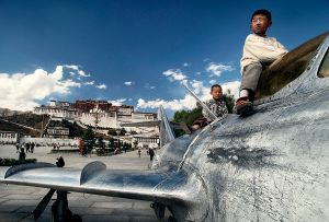 Lhasa, Tibet: Tibetan children are playing on a military airplane, a symbol of occupation that the Chinese authorities erected on the square opposite the Potala palace, a symbol of Tibetan Buddhism.  © Matjaz Krivic