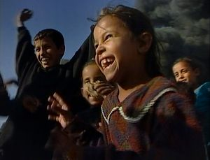 Baghdad, Iraq  (2003).  Irresistible joy.Children, against the burning streets of Sadr City, few days after the crowded Shia neighbourhood of Baghdad changed its name. It used to be called Saddam City.