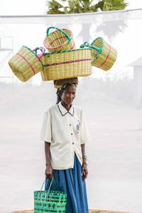 A. Christine: Sells local woven baskets  for 2,000 to 5,000 shillings each. Earns about 10,000 shillings per day.