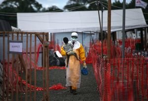 "Suspect. An MSF health worker in protective clothing carries a sick girl at an Ebola treatment center. From the series ""Ebola Crisis Overwhelms Liberian Capital."" Winner of L'Iris d'Or, 2015 Sony World Photography Awards."