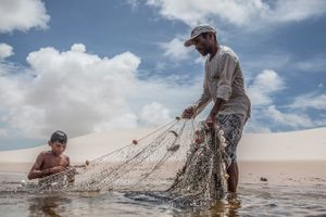 Aldemir Brito fishing with his son Adriel in one of the lagoons close to his house in Queimada dos Britos. The knowledge of living in the dunes is passed from father to son for generations. © Eduardo Leal/4SEE