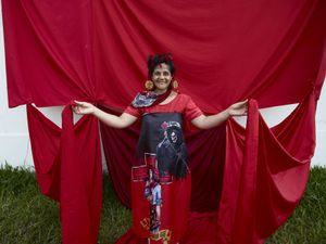 Gauchito Gil devotee happy wrapped in the red coloured flags of the popular saint and wearing earring with the saint icon in the El Yaguarì estancia in Curuzù Cuatià village
