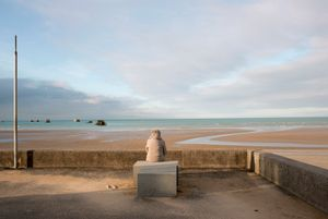 "2014 is a year of significant wartime anniversaries. These photos encourage us to consider the space between our reality and the experience of people involved in the D-Day Landings. The images, made on the D-Day beaches, capture private moments for the strangers who look out to sea. From the series ""and something comes over you..."" © Denise Myers, IdeasTap finalist"