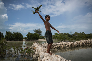 A boy plays with a toy-plane on a sea wall in Eita village.  Many seawalls protect villages of the atoll from the rising seas, however some of them are being constantly destroyed by high tides.
