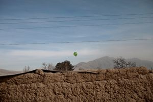 A balloon floats over a camp for internally displaced people on the outskirts of Kabul, Afghanistan, on Thursday, December 17, 2009. © Adam Ferguson