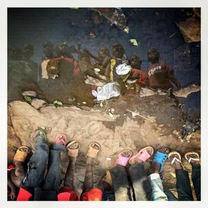 Children are reflected in a puddle in Kibera. The Kibera slum is the largest slum in Nairobi with around half a million inhabitants.