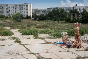 Crimea, Sevastopol. Three young women sunbathe at the edge of a run down Soviet era housing estate by the Black Sea (out of the picture).© Petrut Calinescu