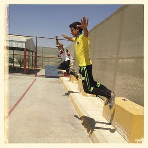 Children jump off concrete blocks in the sports pitch at Za'atari refugee camp