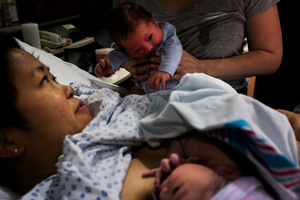 """Emily holds the new-born baby to meet his new little brother. Reid and Eddie were born only four days apart, despite being due three weeks apart. Both babies had the same donor, making them biological half-brothers. """"Oh my God,""""Kate said, """"we're…like…a family, suddenly!"""" New York, New York, USA, 13December 2015."""
