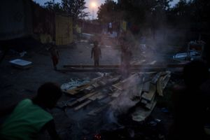 Children play near a garbage burn pile in the Stara Gazela camp at dusk. © Matt Lutton
