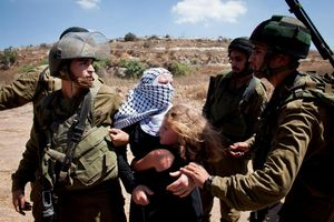 Israeli soldiers arrest Narian Tamimi, as her daughter hugs her trying to stop her arrest, during the weekly protest against the Separation Wall and the occupation, 2012.