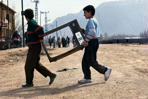 Two Kurdish boys cross a road, carrying the frame of a television screen. Dogubayazit, Kurdistan/Turkey, 1993.