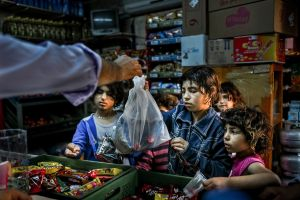 Kids buy snacks from a local department store with the money they got by begging. These children will be lucky if they have the chance to eat a real meal today. © Turjoy Chowdhury