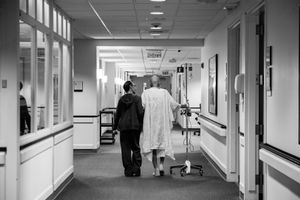 Recovering from a collapsed lung and managing a recent pneumonia diagnosis, Howard Borowick takes a walk down the hallways of Medical Oncology with the assistance of wife, Laurel Borowick, left, by his side. Greenwich, Connecticut. November, 2013 © Nancy Borowick