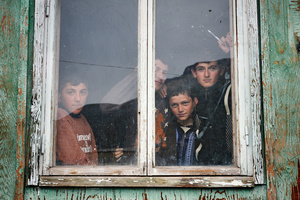 Boys glipsing out of the window of a schoolhouse in Mirashkhani.