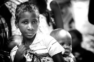 Mozambican girl carrying her brother. There are an estimated 1.8 million orphans in Mozambique, of which 510,000 are due to AIDS.