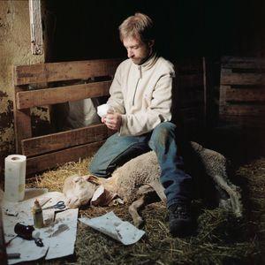 Olivier nursing a sheep, Ardèche, France, 2010 © Antoine Bruy