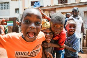 Children surround me in a street in Freetown.