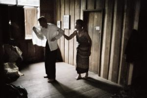 District of Lampang, Thailand 2005. Wife helping her blind husband to get dressed.