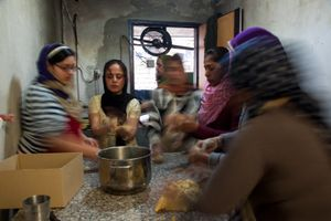 Women sing while preparing lunch at the Sikh Temple in a northern suburb of Rome.