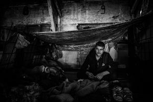 """View of the inside temporary """"room"""" in a barrack in Serbia, Belgrade. During the rain the roof is leaking, so man made a roof from plastic. Belgrade, Serbia."""