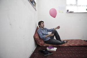 "In his room, Shamsul Aziz plays with a pink ballon, a souvenir from ""We believe in Balloons"", an happening organized by a US-Colombian artist.  Hundreds youngsters released a thousand balloons in the street of Kabul in May 2013 