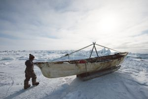 "Seven-year old Steven Reich examines his father's umiaq, or skinboat used for whaling. His father Tad, captain of Yugu crew, expresses nervous excitement to bring Steven out whaling on the ice for the first time: ""I am proud of my son; he's here to learn to be a hunter."""