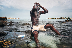 Kherou, a young wrestling champion, performs a ritual in the water of the sea while pouring milk over his body in order to obtain the reinforcement of a ghost who lives in the stones at the shore. Dakar, Sierra Leone, 11 August 2015.
