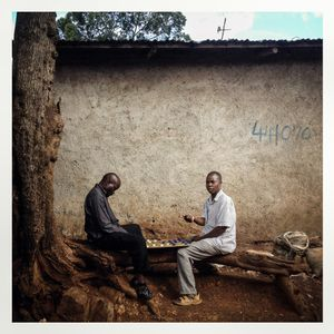 Men plays checkers in Kibera. The Kibera slum is the largest slum in Nairobi with around half a million inhabitants.