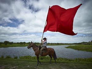 Gaucho flying the Gauchito Gil red coloured flag in the El Yaguarì estancia in Curuzù Cuatià village