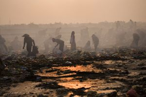 Recycling workers scavenge amongst the rubbish, as dawn breaks over Smokey Mountain. © Nigel Dickinson.