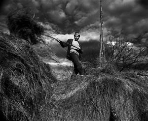 Petru and the Claie, Sirbi, 1999. The quality of a haystack can be told by its color. The quality of a man by the time it takes him to bring one home. © Kathleen Laraia McLaughlin.