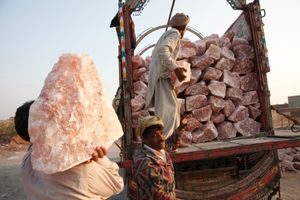 Men load large chunks of pink rock salt on to trucks at a salt distribution area next to Khewra Salt mine.