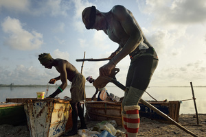 The salt miners prepare their boats and tools in the early morning before starting to mine the salt in the lake.